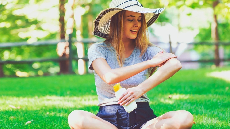 Sonnenschutz: Eine junge Frau mit Sonnenhut in Shorts und T-Shirt sitzt auf dem Rasen und cremt den Arm mit Sonnenschutzmittel ein.